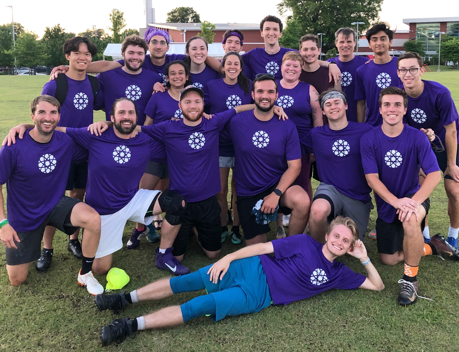A large group of ultimate frisbee players wearing purple jerseys showing the MUDA icon